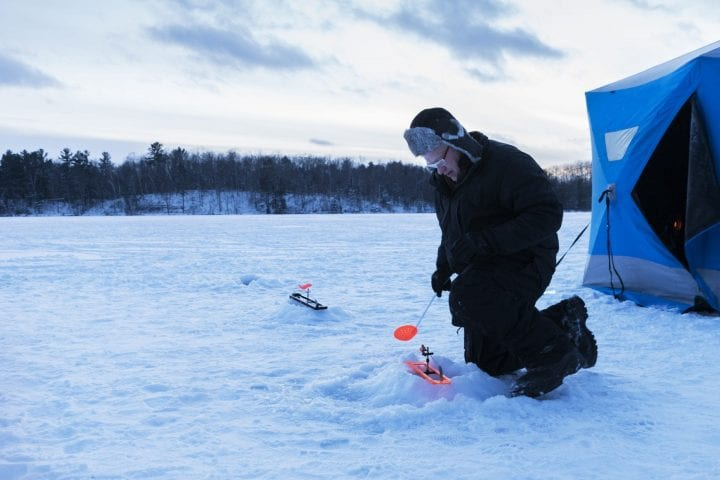 Caucasian man in 50's checks an ice fishing hole at dusk on a winter afternoon in northern Minnesota, USA