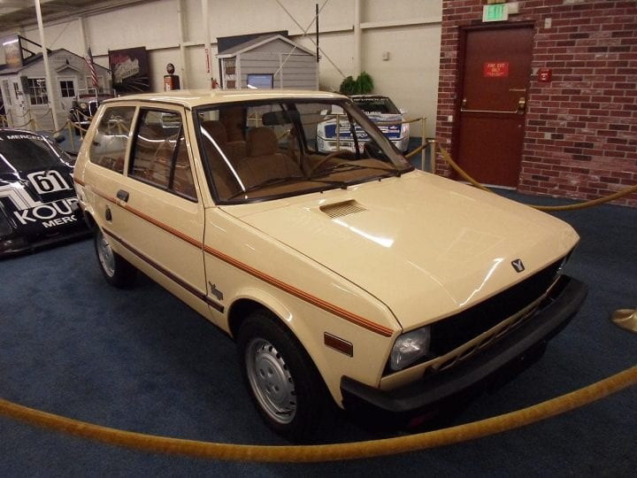 a yugo car that is being placed on display