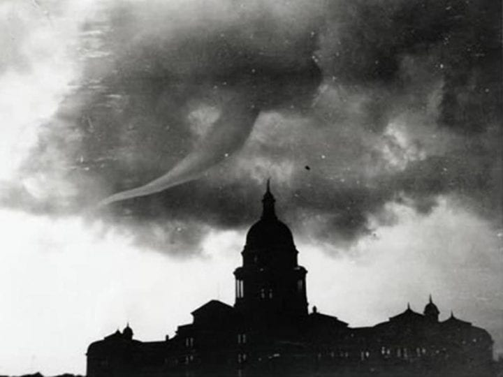 a tornado emerges over a building in black and white