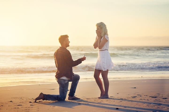 man proposing to woman on the beach