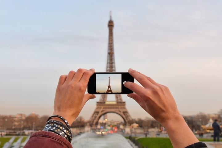 someone taking a photo of the eiffel tower