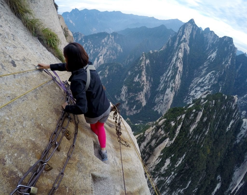 woman walking along a rock embedded in the mountains
