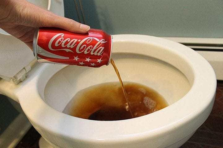 somebody pouring coke into a toilet