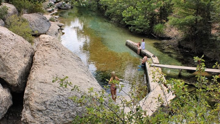 some people standing around at jacob's well in texas