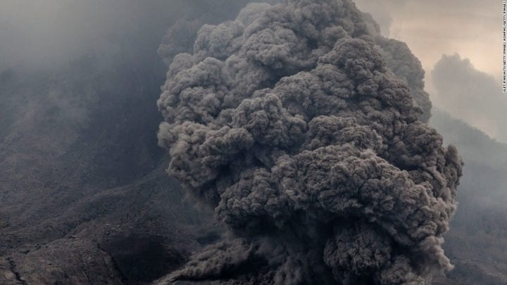 a volcano explodes and ejects lots of smoke and gas