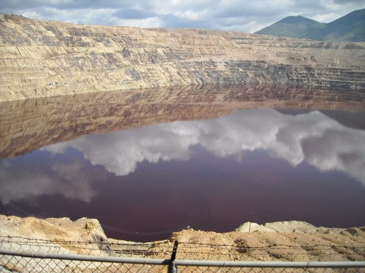 a brown lake that is reflecting the clouds