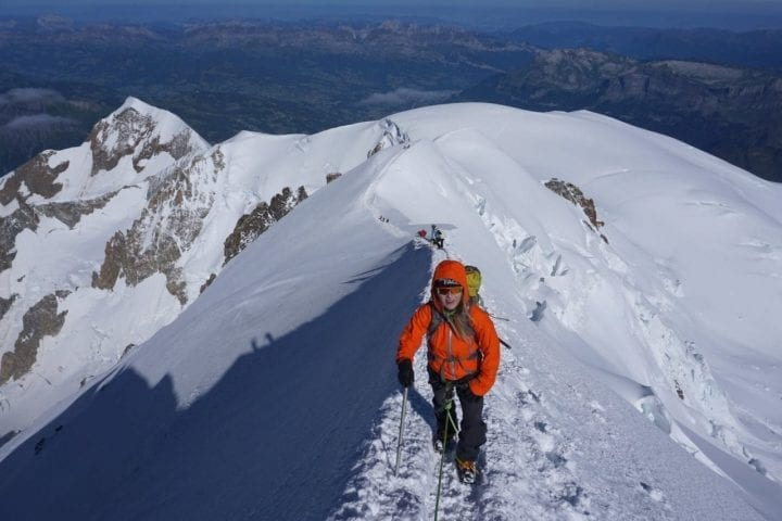 woman climbing icy and snowy mountain