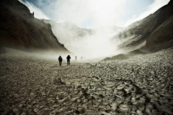 a group of people hike up a misty mountain