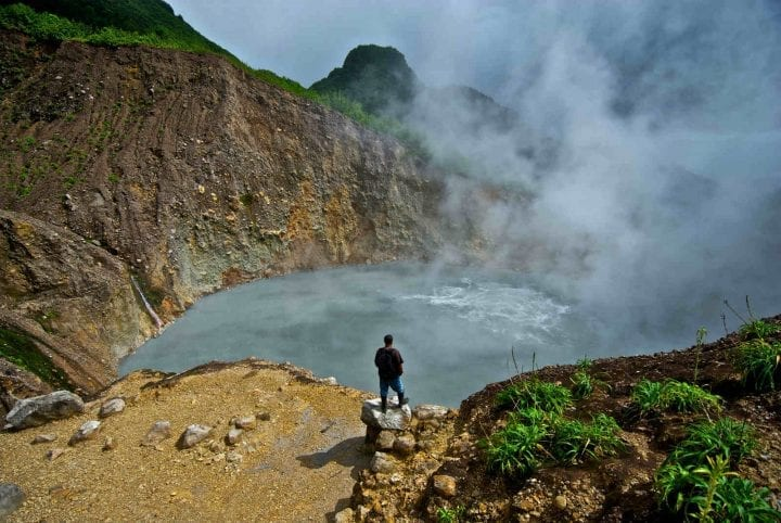 man stands in front of boiling lake