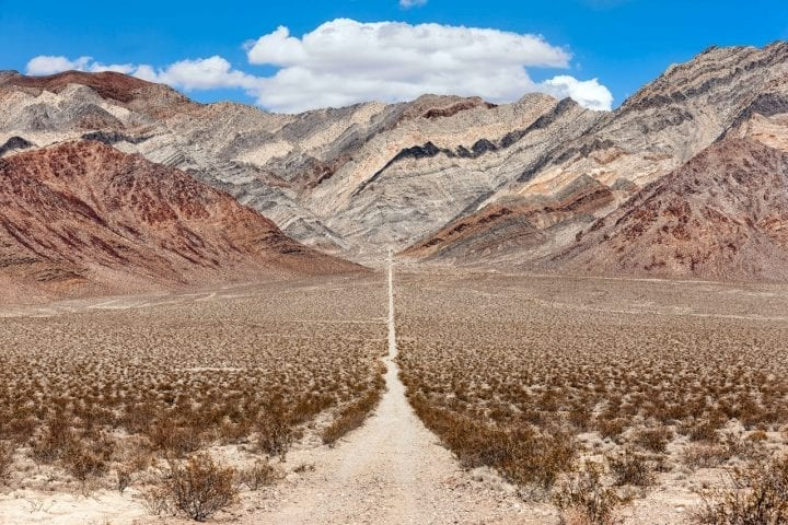 a long, narrow road that leads to colored mountains