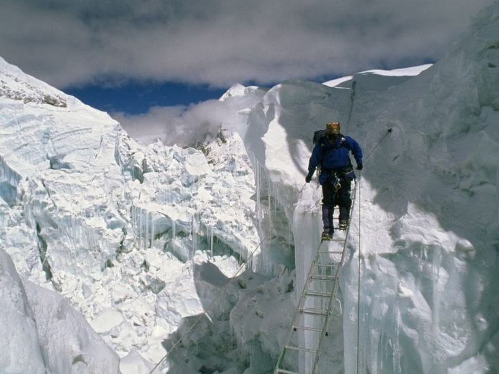 man walks across ladder above ice