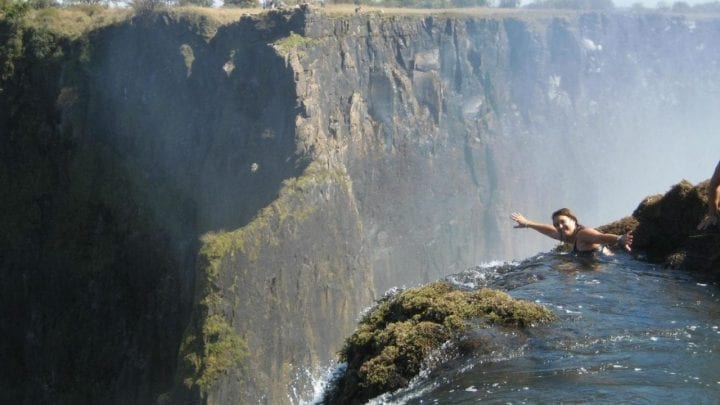 woman dangles precariously over edge of waterfall