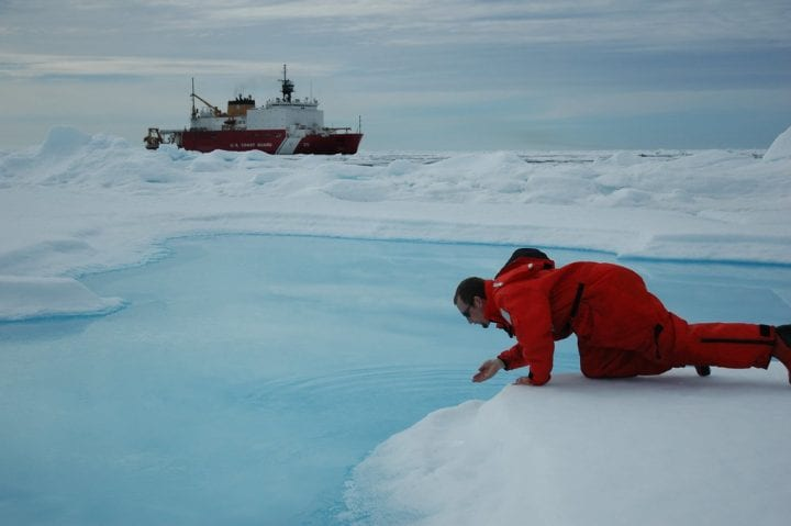 A man in the arctic north sampling the water temperature with boat in the distance