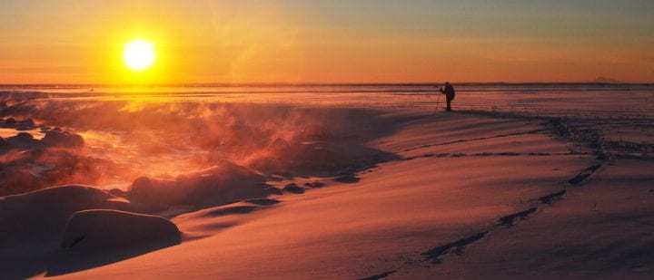 a man hikes on the snow during sunset