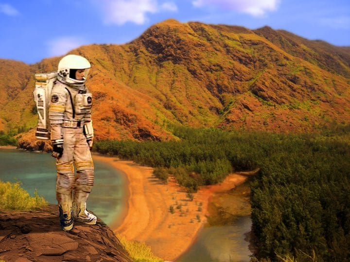 astronaut looks forlornly at the desert ground