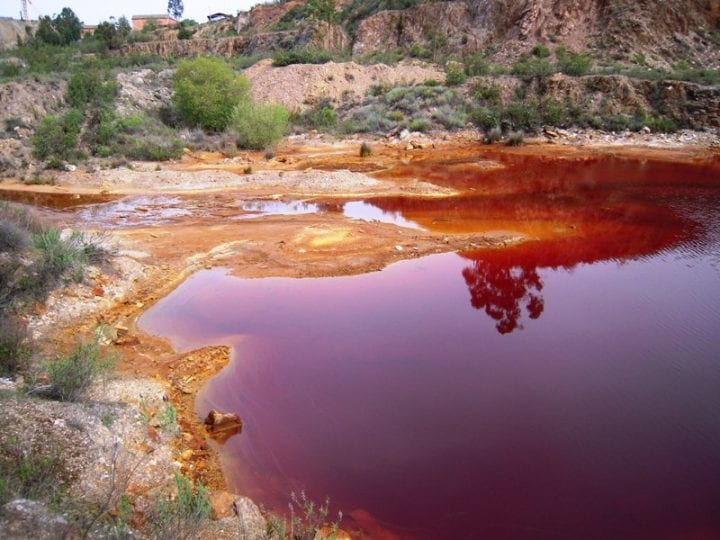 Brownish-red contaminated water in a small lake in a dry, arid landscape