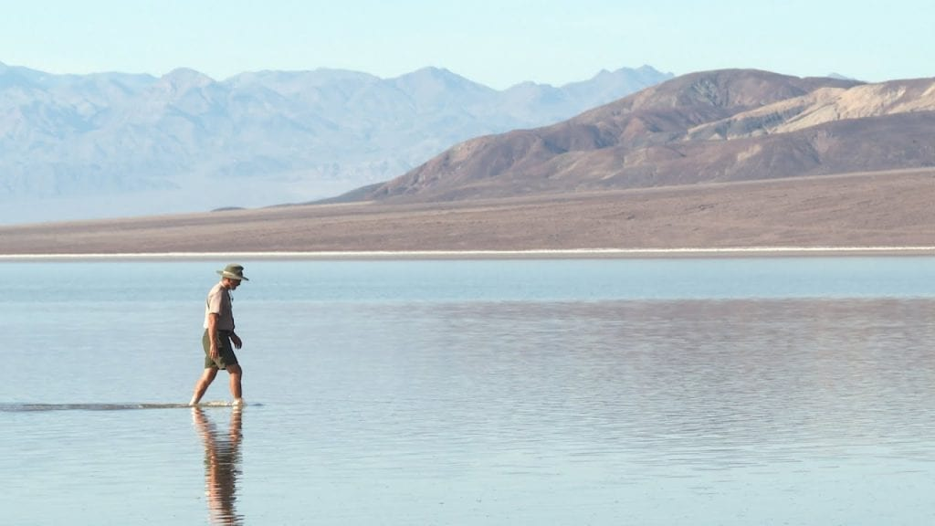 a man walking in the water of death valley lake