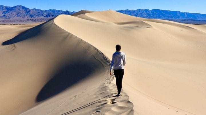 woman walking across the sand dunes in death valley
