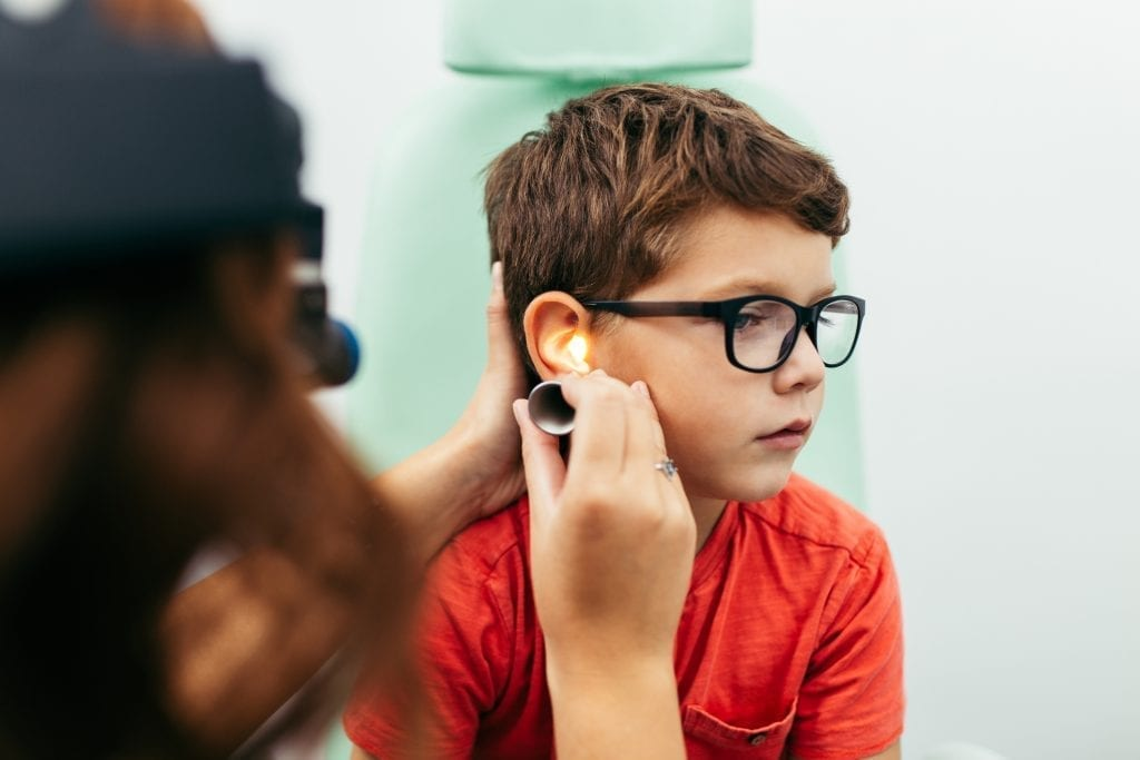 Young boy at medical examination or checkup in otolaryngologist's office