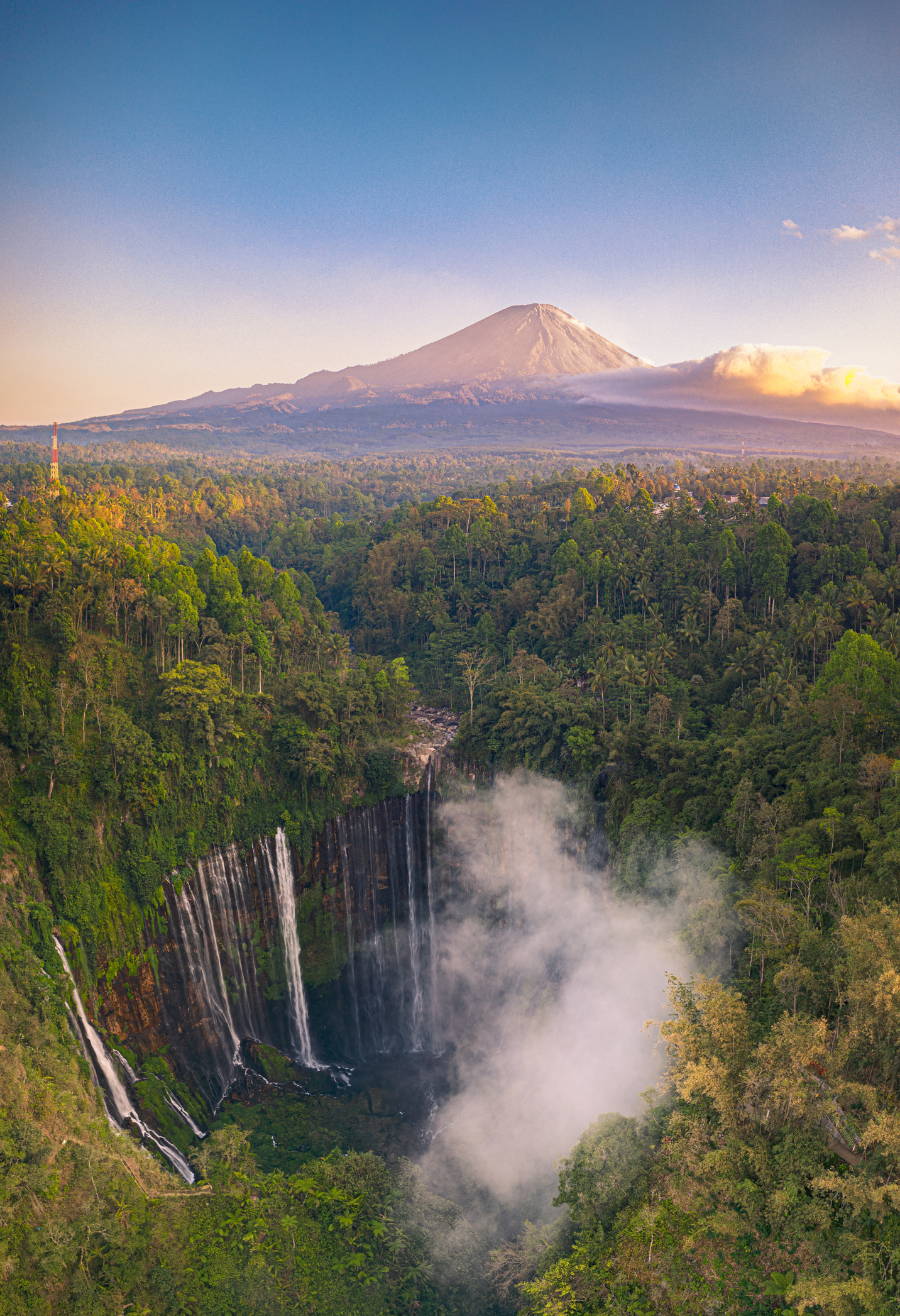Aerial view of Tumpak Sewu Waterfall with Mount Semeru in the background in early morning sunrise time, East Java, Indonesia.