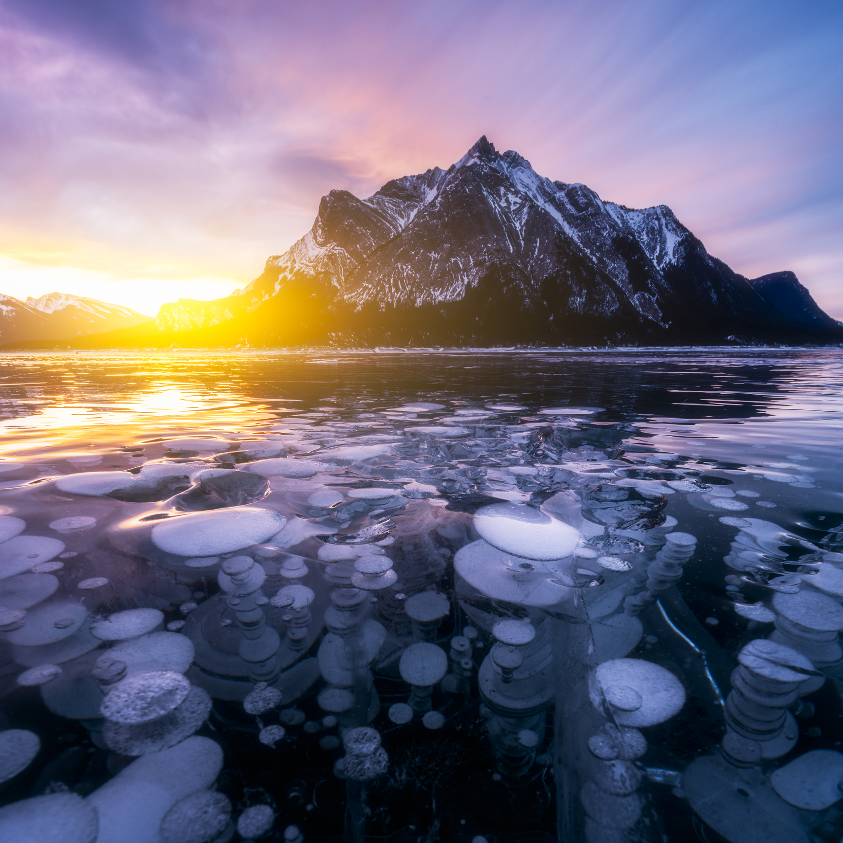 methane bubbles trapped in ice in Abraham Lake in sunrise in winter, AB, Canada.