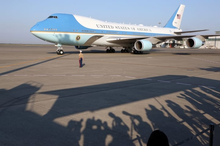 Air Force One parked on Runway with soldier standing next to it.