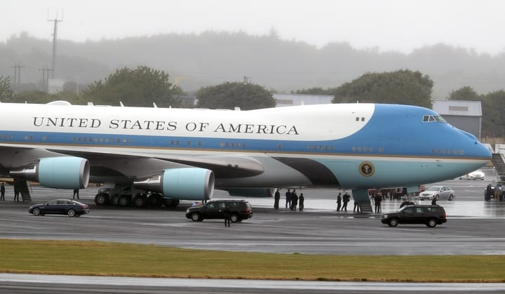 Air Force One parked on runway with presidential fleet