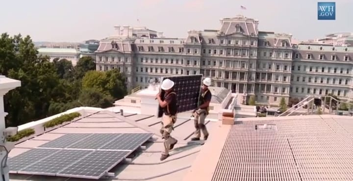 Workers installing solar panels on the White House roof