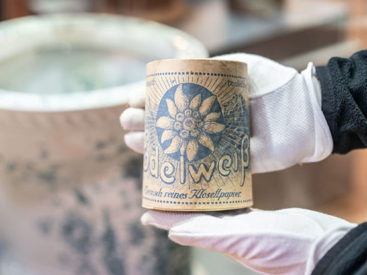 "A roll of toilet paper from the first half of the 20th century of the brand ""Edelweiss"" in the hand."