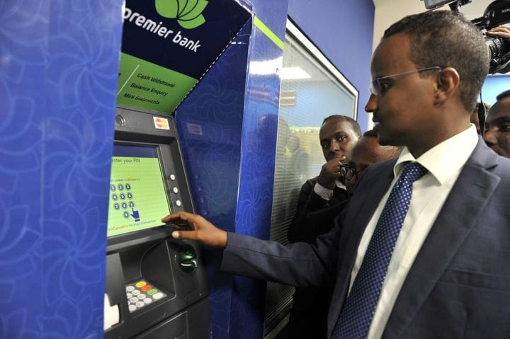 Somalia Interior Minister, Abdirahman Mohamed Hussein, withdraws cash from an ATM during the opening ceremony of Premier Bank in Mogadishu, Somalia, on 21 May 2015. AMISOM Photo/Omar Abdisalam
