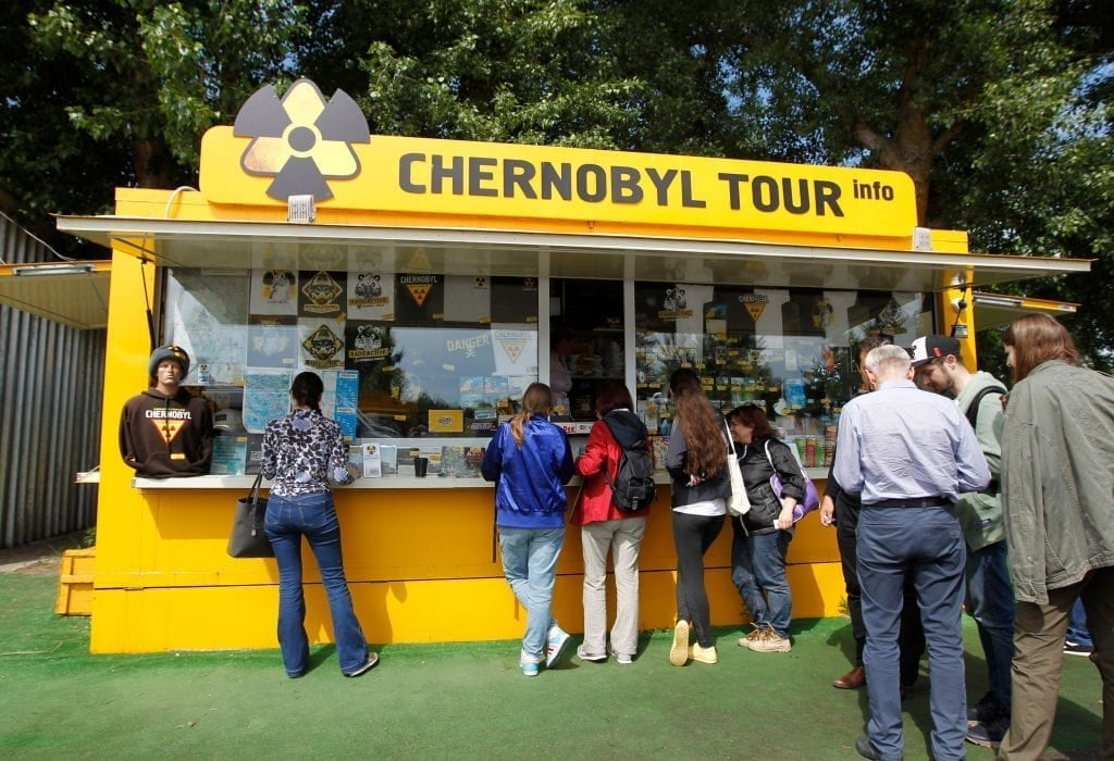 Visitors seen standing next to a shop with Chernobyl souvenirs on the Dytyatky checkpoint at the Chernobyl exclusion zone in Pripyat.