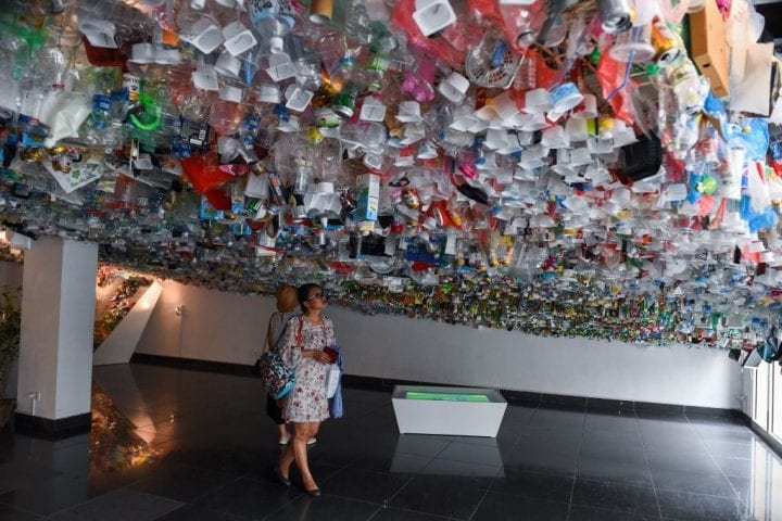 Visitors view a hanging art installation by a group of artists made from scraps of plastics, cans and containers