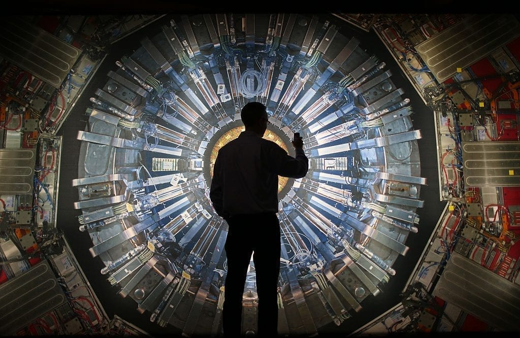 visitor takes a phone photograph of a large back lit image of the Large Hadron Collider (LHC) at the Science Museum's 'Collider' exhibition