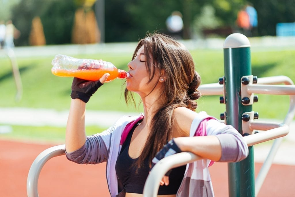 Young woman exercising and resting and drinking energy drink outdoors on sunny summer day in training outfit