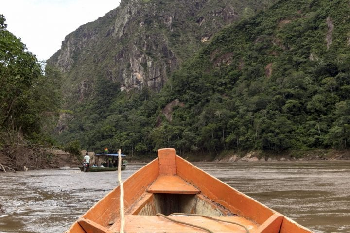Contrast or orange wooden boat front and green jungle landscape, sailing in the muddy water of the Beni river, rainforest of Amazon river basin in Bolivia, South America