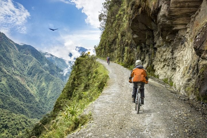 "Bike adventure travel photo. Bike tourists ride on the ""road of death"" downhill track in Bolivia. In the background sky circles a condor over the scene."