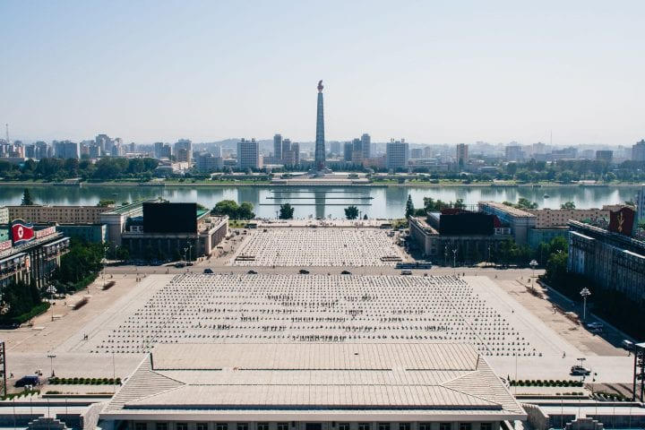 The view across Pyongyang from Kim Il-sung Square on a sunny day with a view of the Juche Tower and Taedong River in the distance.