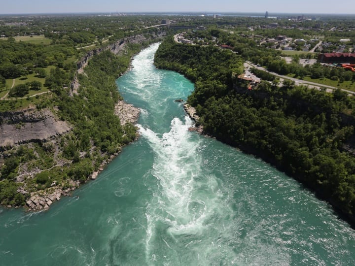 The Niagara River emerges from the Niagara Gorge on June 4, 2013 at Lewiston, New York. The river forms the border between the United States (L), and Canada and drains Lake Erie into Lake Ontario. The river is a major source of hydroelectric power for the region. The aerial view was seen from a helicopter flown by the U.S. Office of Air and Marine, (OAM), which monitors and patrols the U.S. northern border with Canana.