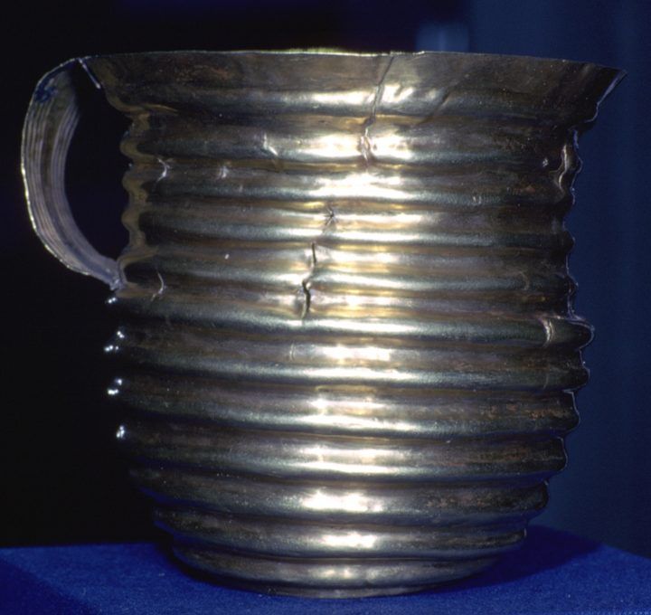 The Rillaton Gold Cup, Early Bronze Age, 1700-1500BC, from Rillaton, Cornwall, England. Rillaton barrow was excavated in 1837 and found to contain an inhumation beneath the 25m wide barrow. The burial had been placed in a stone cist and human remains were discovered along with grave goods including a bronze dagger, beads, pottery, glass and other items. The burial also contained the Rillaton Gold Cup, a biconical gold vessel, 90mm high, with a handle attached with rivets. The cup resembles a late Neolithic ceramic beaker with corded decoration. The cup is of note due to its Aegean style metalwork of the period and resembles similar finds from the Greek site of Mycenae, suggesting cultural and trading links with the Eastern Mediterranean. The cup became lost after discovery but turned up years later in the dressing room of King George V as a receptacle for his collar studs. It is now on show the British Museum, next to the similar Ringlemere Cup, though it belongs to the Royal Collection. An exact copy may be seen in the Royal Cornwall Museum at Truro. (Photo by CM Dixon/Print Collector/Getty Images)
