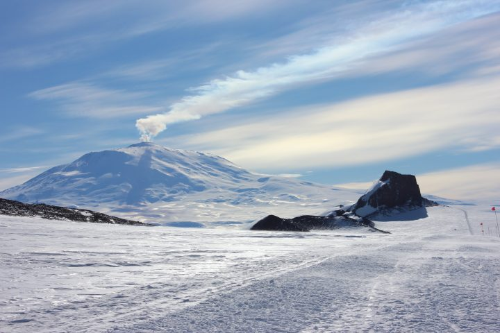 Smoldering Mt Erebus, the worlds most southern active volcano, with its plume being carried away in the winds. Castle Rock in the foreground is an old volcano plug.