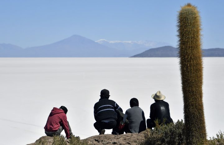 TOPSHOT - Men observe the Salar de Uyuni, the world's largest salt flat, in the Altiplano in southwestern Bolivia, on September 28, 2019. (Photo by Aizar RALDES / AFP) (Photo credit should read AIZAR RALDES/AFP via Getty Images)