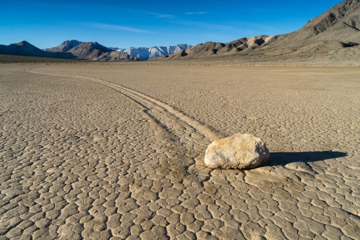 """The Racetrack Playa, or The Racetrack, is a scenic dry lake feature with """"sailing stones"""" that inscribe linear """"racetrack"""" imprints. It is located above the northwestern side of Death Valley, in Death Valley National Park, Inyo County, California, U.S."""