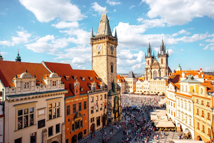 Cityscape view on the clock tower and Tyn cathedral on the old square in Prague.