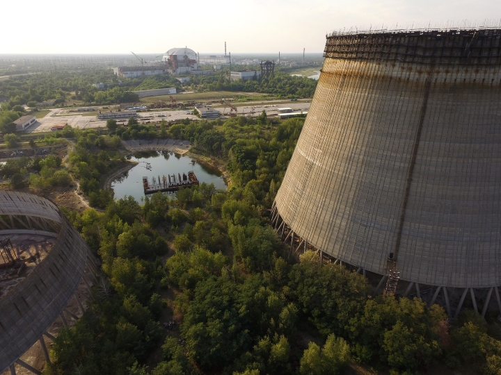 In this aerial view two partially-constructed and abandoned cooling towers stand as the new enclosure built over stricken reactor number four is seen in the distance behind at the Chernobyl nuclear power plant on August 19, 2017 near Chornobyl', Ukraine. On April 26, 1986 reactor number four exploded after a safety test went wrong, spreading radiation over thousands of square kilometers in different directions. Ukraine and Belarus are still challenged by the consequences of the accident, with huge swaths of territory that remain uninhabitable as well as ongoing health effects for their populations.