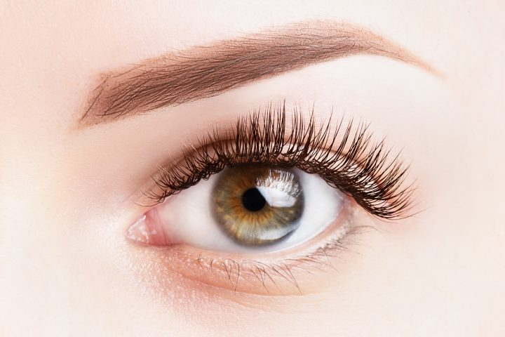 Female eye with long eyelashes. Classic eyelash extensions and light brown eyebrow close-up. Eyelash extensions, lamination, microblading, tattoo, permanent, cosmetology concept.
