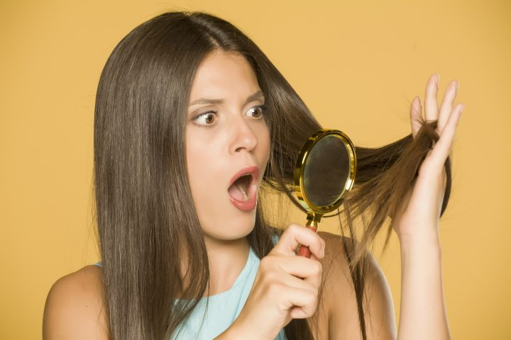 Shocked young woman looking at her hair with magnifying glass on yellow background