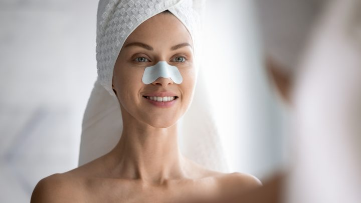 Happy beautiful young woman wrap towel on head apply white nose strip mask look in bathroom mirror, smiling attractive lady cleansing face pores blackheads, healthy clean skin care treatment concept