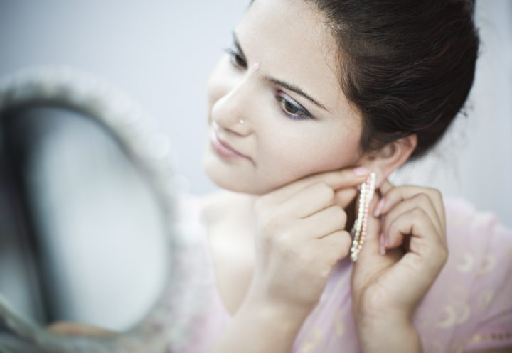 Close-up of a beautiful young woman of Indian ethnicity putting on earring and looking at a small round mirror. She is dressed in light pink sari and blouse which is a traditional Indian dress typically for a married Indian woman. Horizontal indoor image with copy space and selective focus at aperture f/1.4.