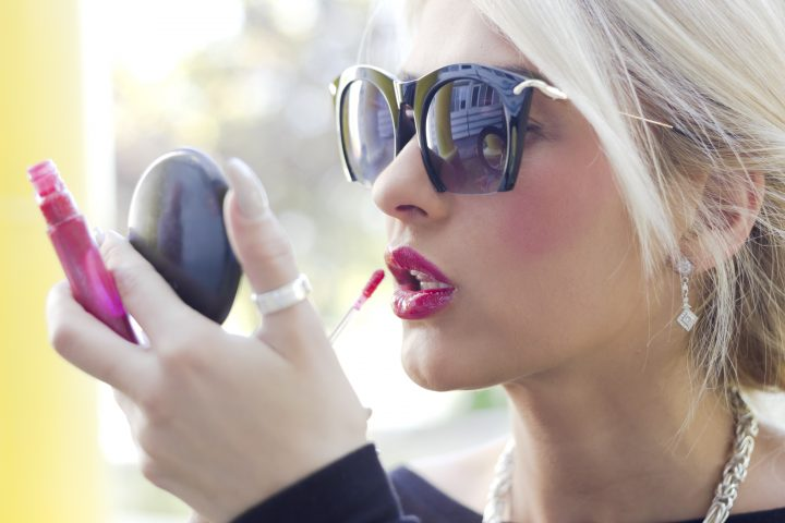 Beautiful blonde girl applying lip gloss over red lipstick. Close up photo taken with dslr camera. Natural light.