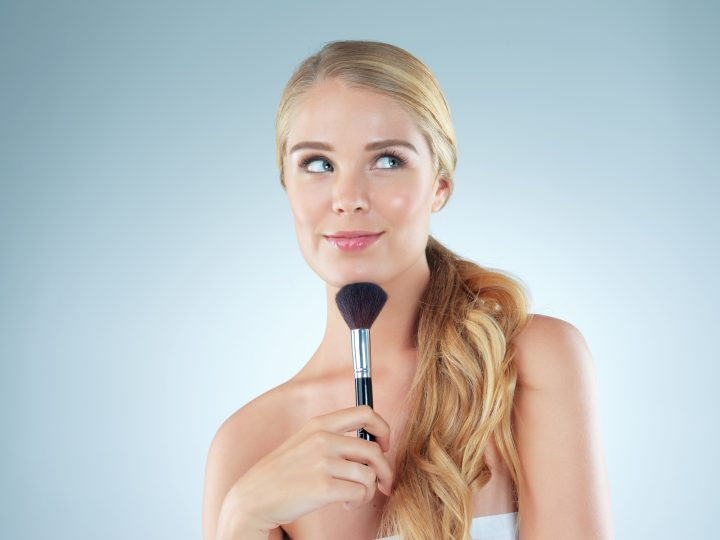 Studio shot of a beautiful young woman holding a makeup brush against a blue background